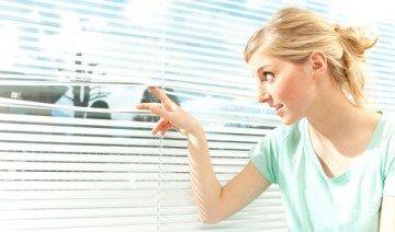 beautiful casual blond woman in venetian window background